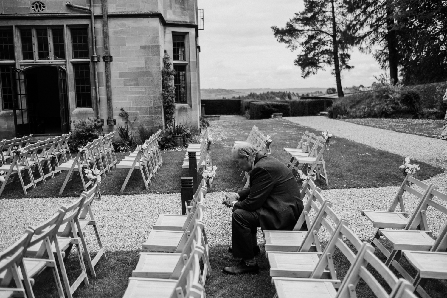 black and white of man sitting on a chair before the outdoor wedding ceremony at Coombe Lodge Blagdon