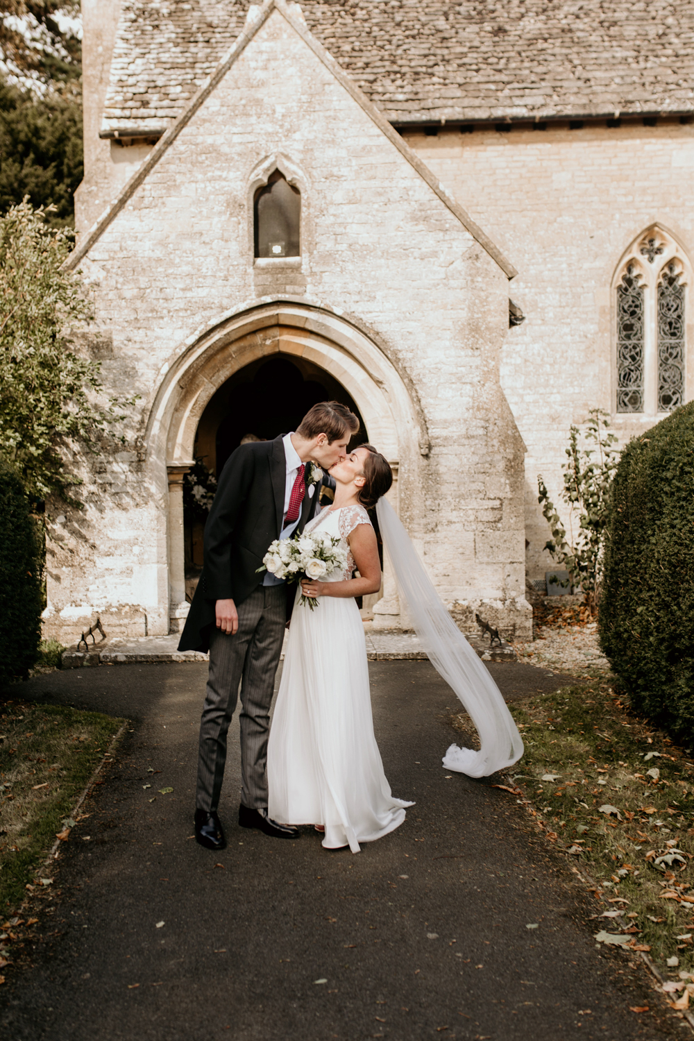 bride and groom first kiss outside church after their Poulton wedding ceremony