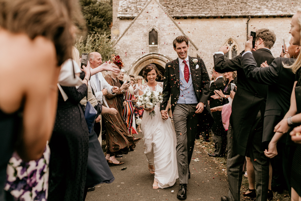 bride and groom walking through confetti after Poulton wedding ceremony