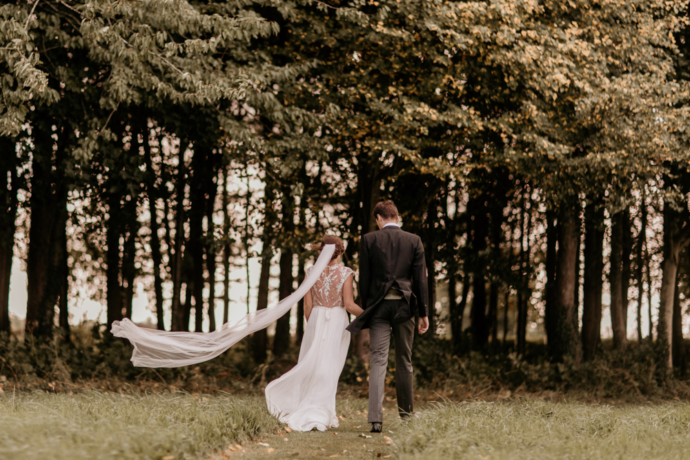 bride and groom walking towards a forest for their Poulton wedding