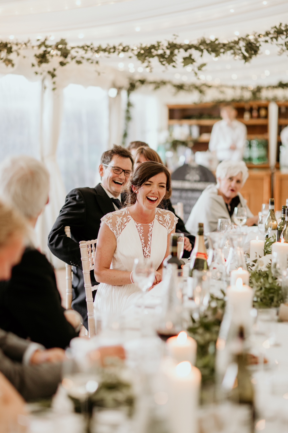 bride laughing during speeches for her marquee Poulton wedding