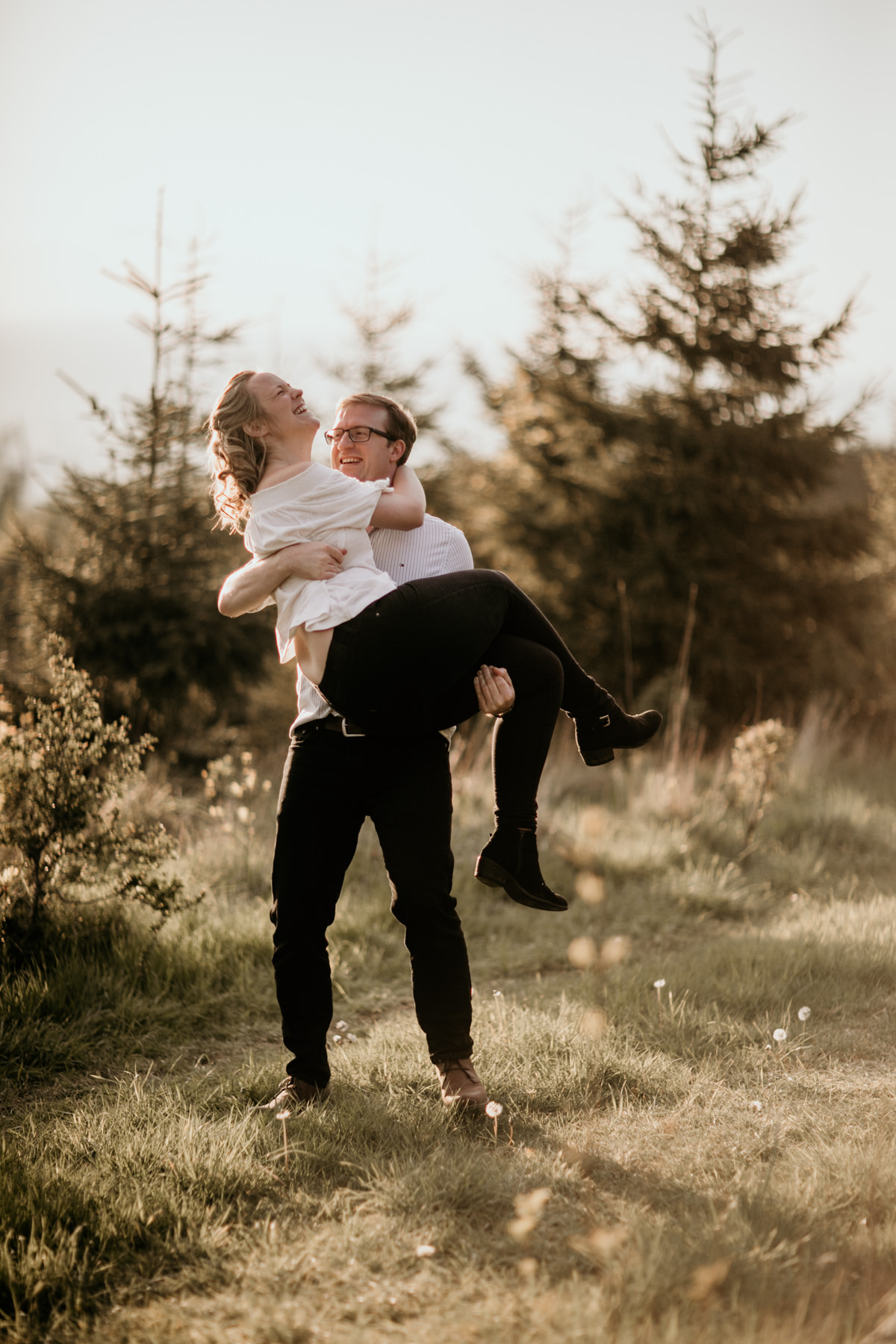guy lifting his fiance in his arms during the cotswolds countryside engagement session
