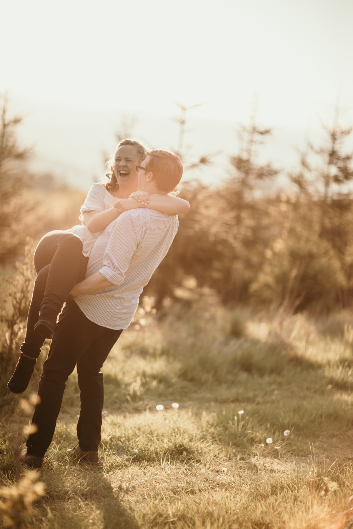 guy lifting up his fiance during their cotswolds engagement shoot