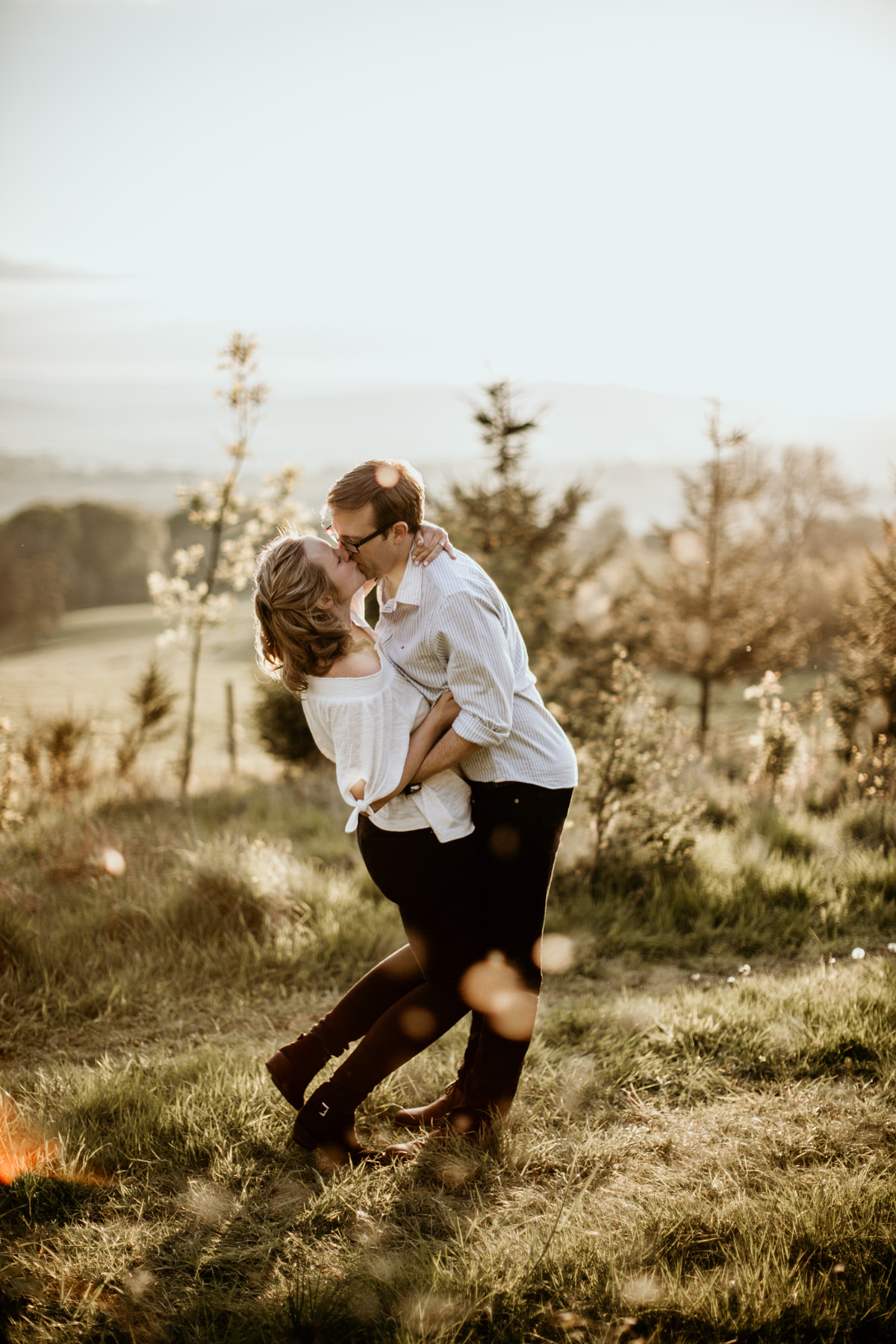 couple kissing on a field at sunset light during the cotswolds countryside engagement session