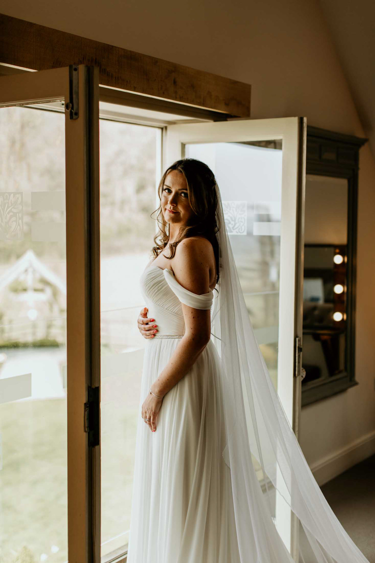 bride in the doorway of hyde house wedding venue in the cotswolds