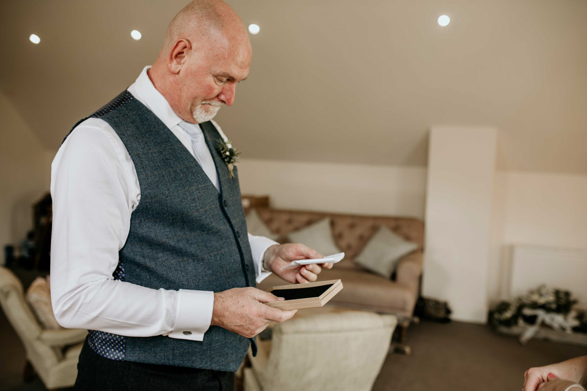 bride offering her dad a wedding gift before her wedding day