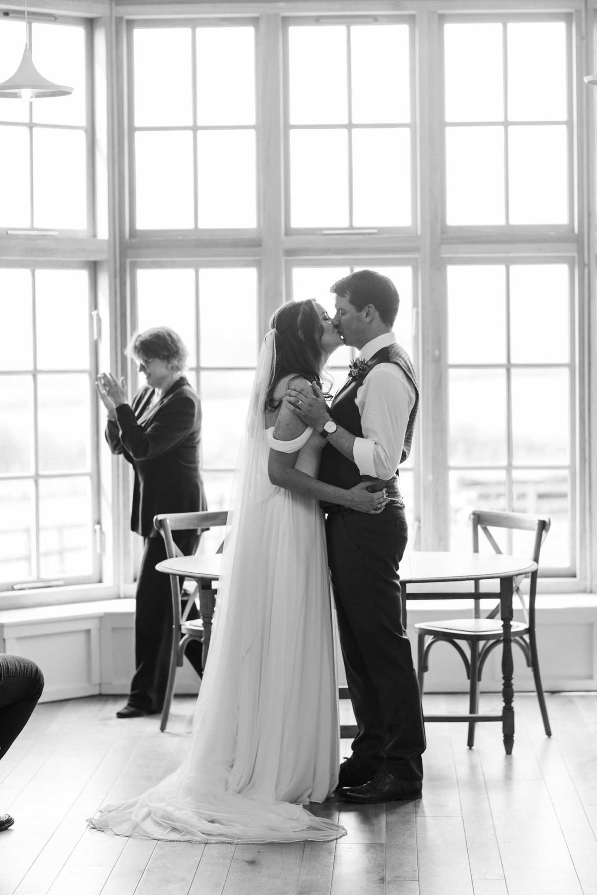 black and white image of wedding ceremony first kiss at the grange