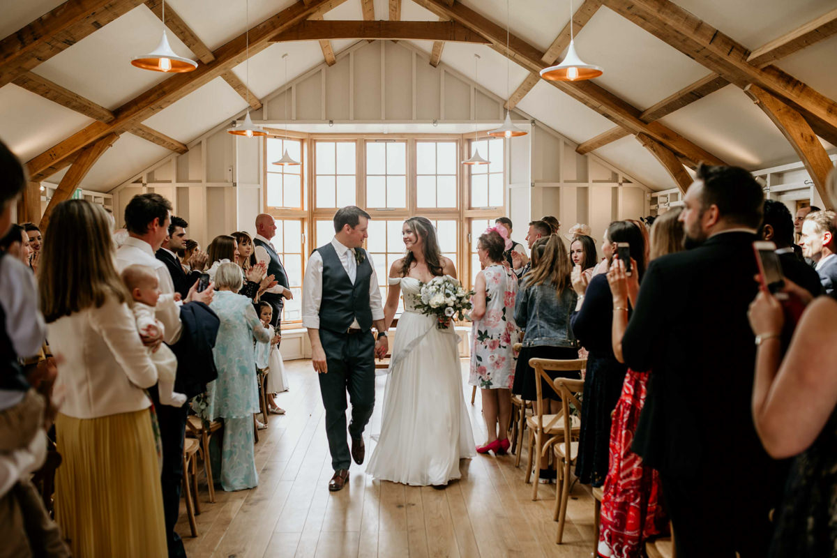 bride and groom walking down the aisle at the grange in hyde house