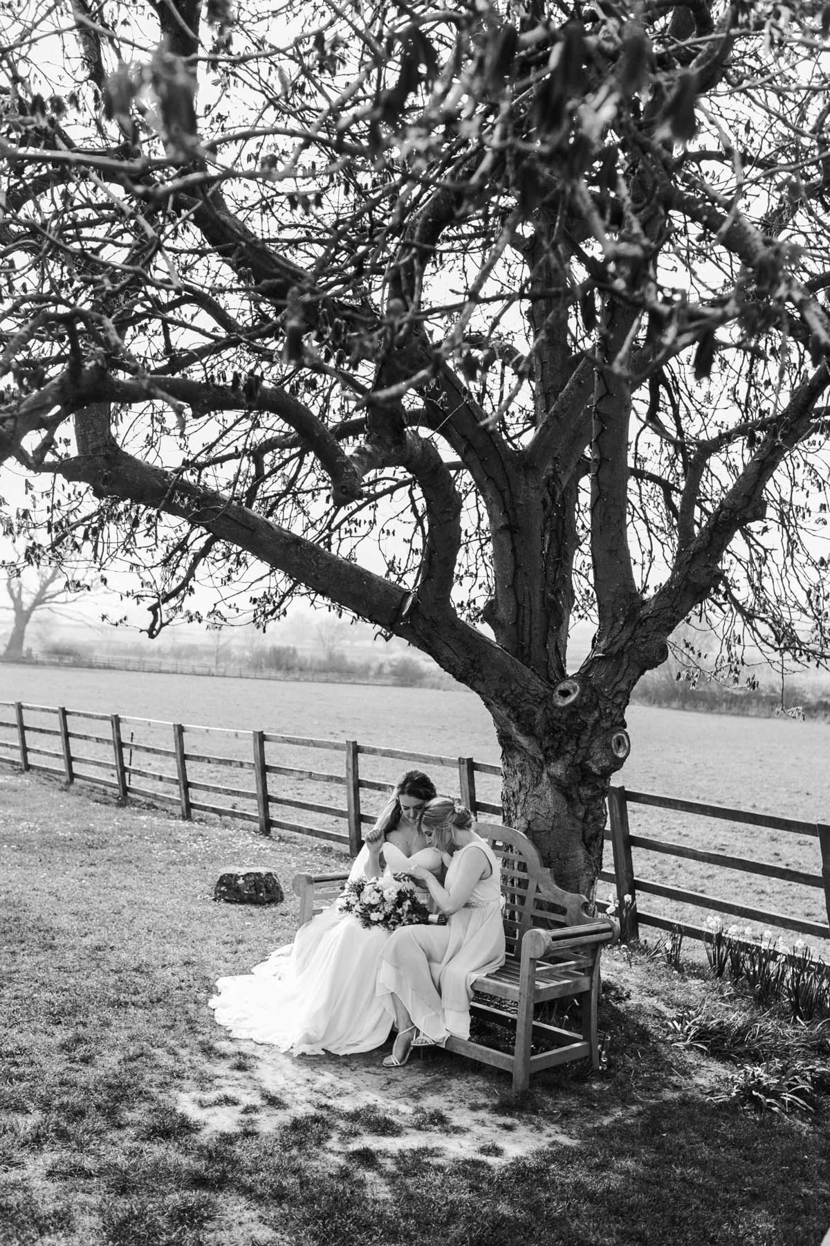 black and white image of bride and bridesmaid after the wedding ceremony at the grange, hyde house cotswolds