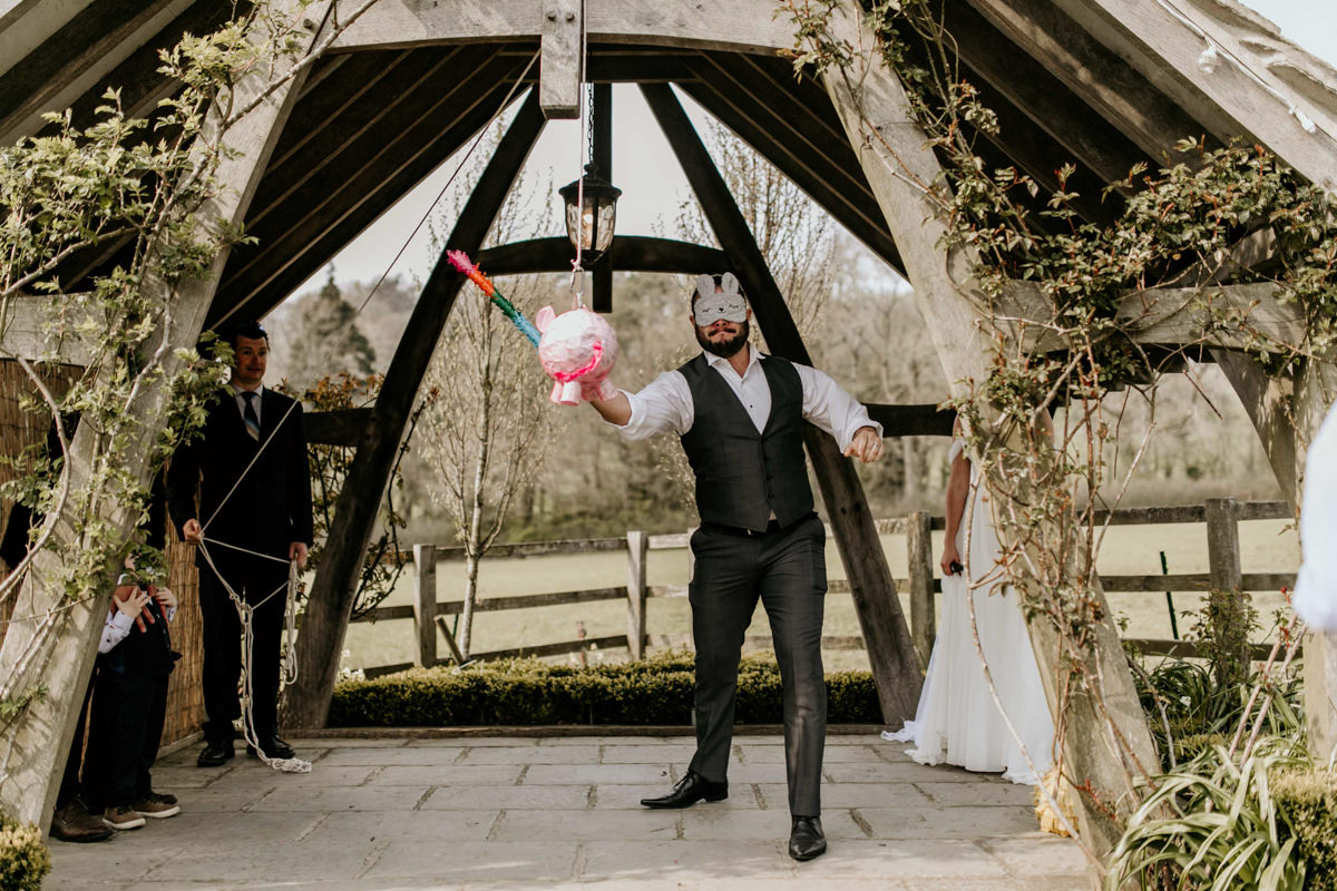 guest hitting a confetti cake at hyde house wedding venue