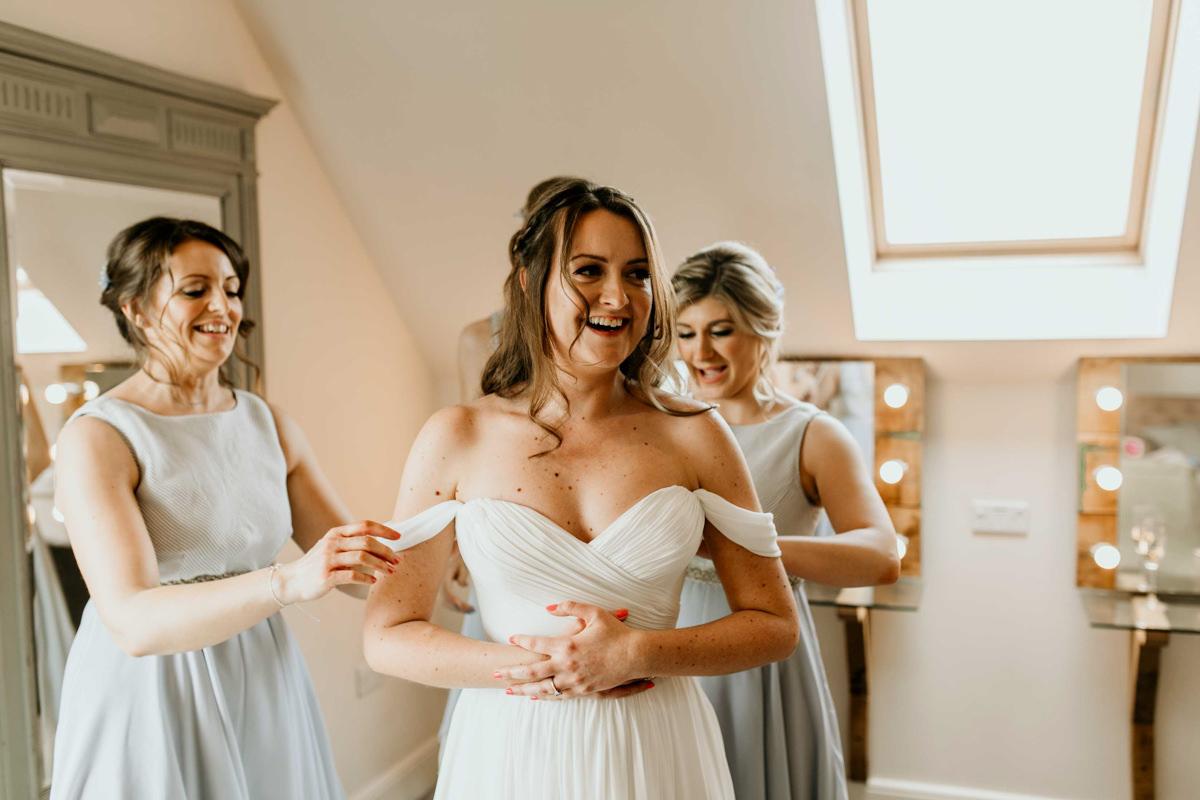 bride getting her enzeaoni wedding dress on