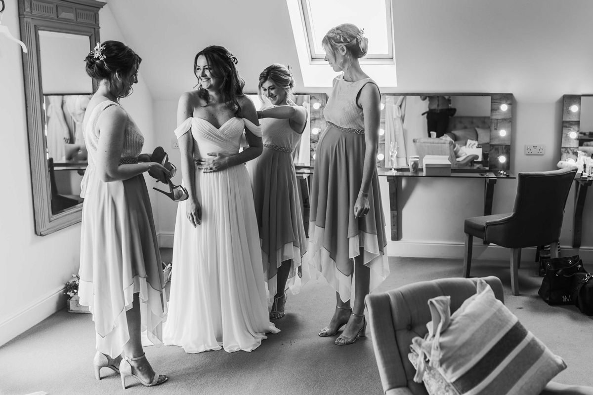 black and white image with bride and bridesmaids before the wedding ceremony
