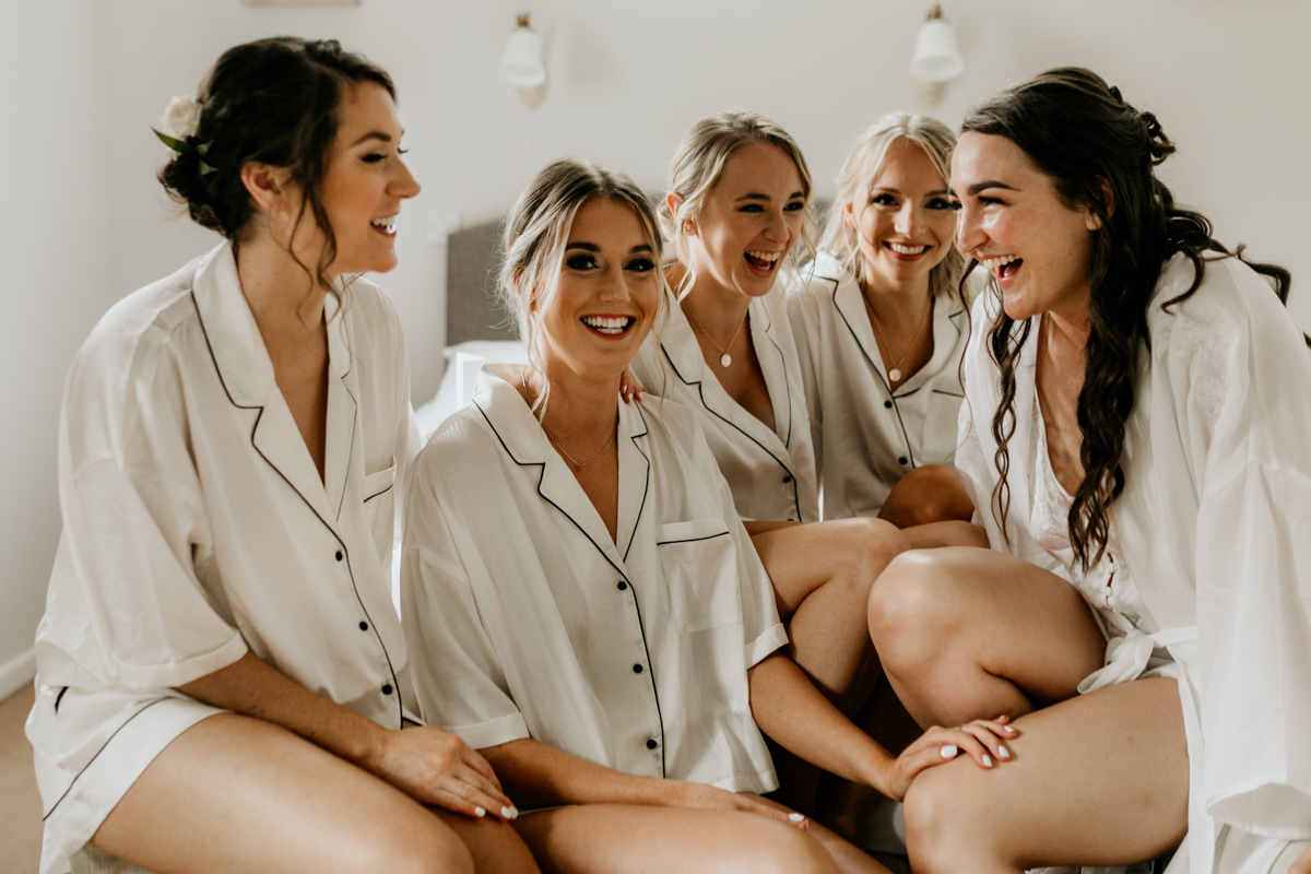 bride and bridesmaids wearing matching white silk pyjamas