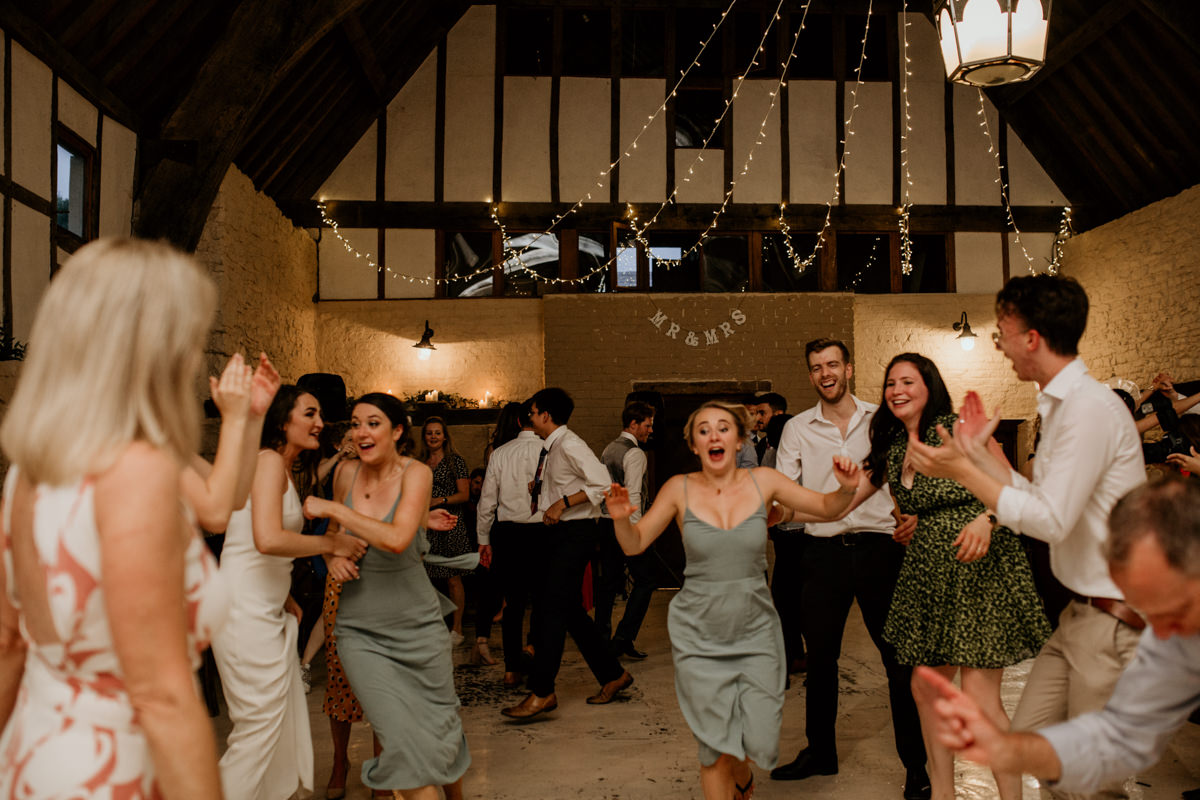 guests dancing to ceilidh music during the wedding reception at Priors Court Barn