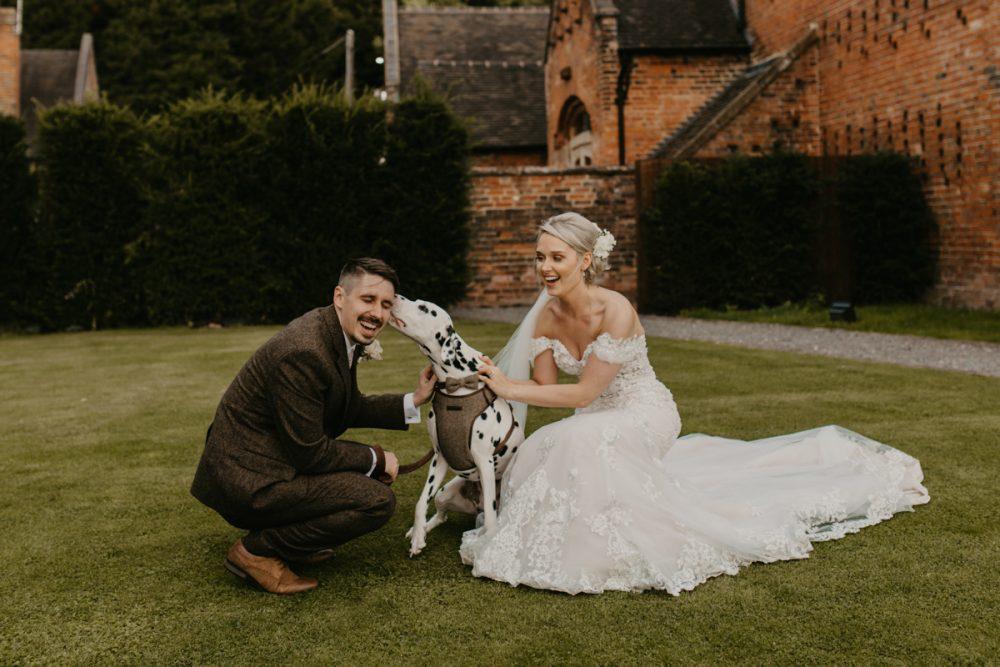 bride and groom outside shustoke barn with their dog, during their barn wedding