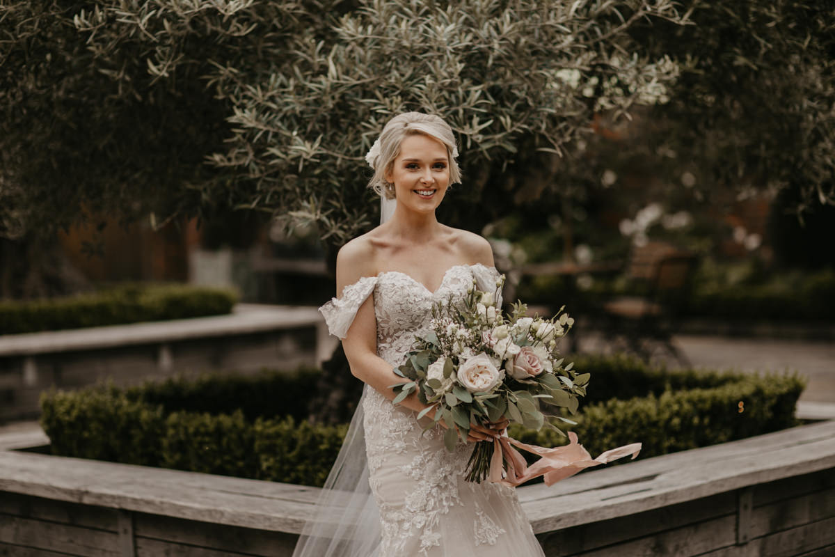 bride holding flowers in the garden of Shustoke Barn wedding venue with olive trees behind