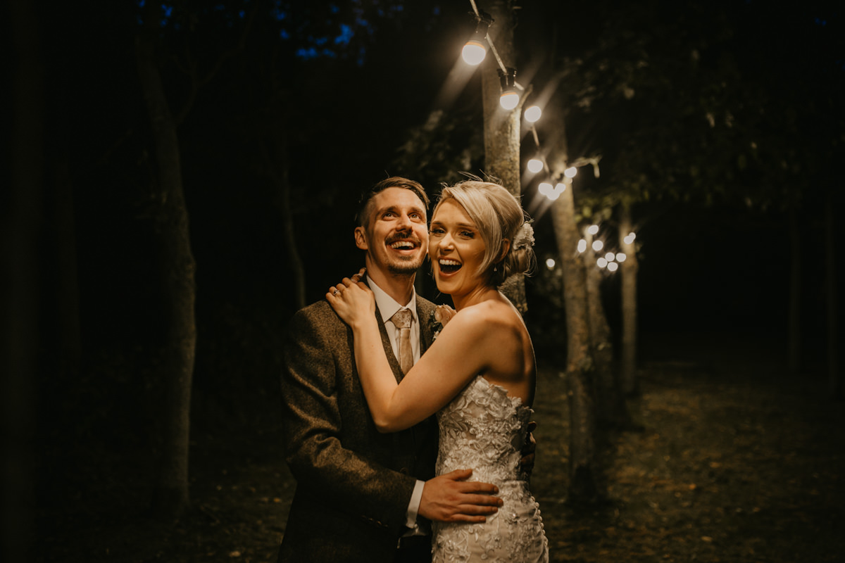 bride and groom portraits in the evening with the lights outside Shustoke Barn wedding venue