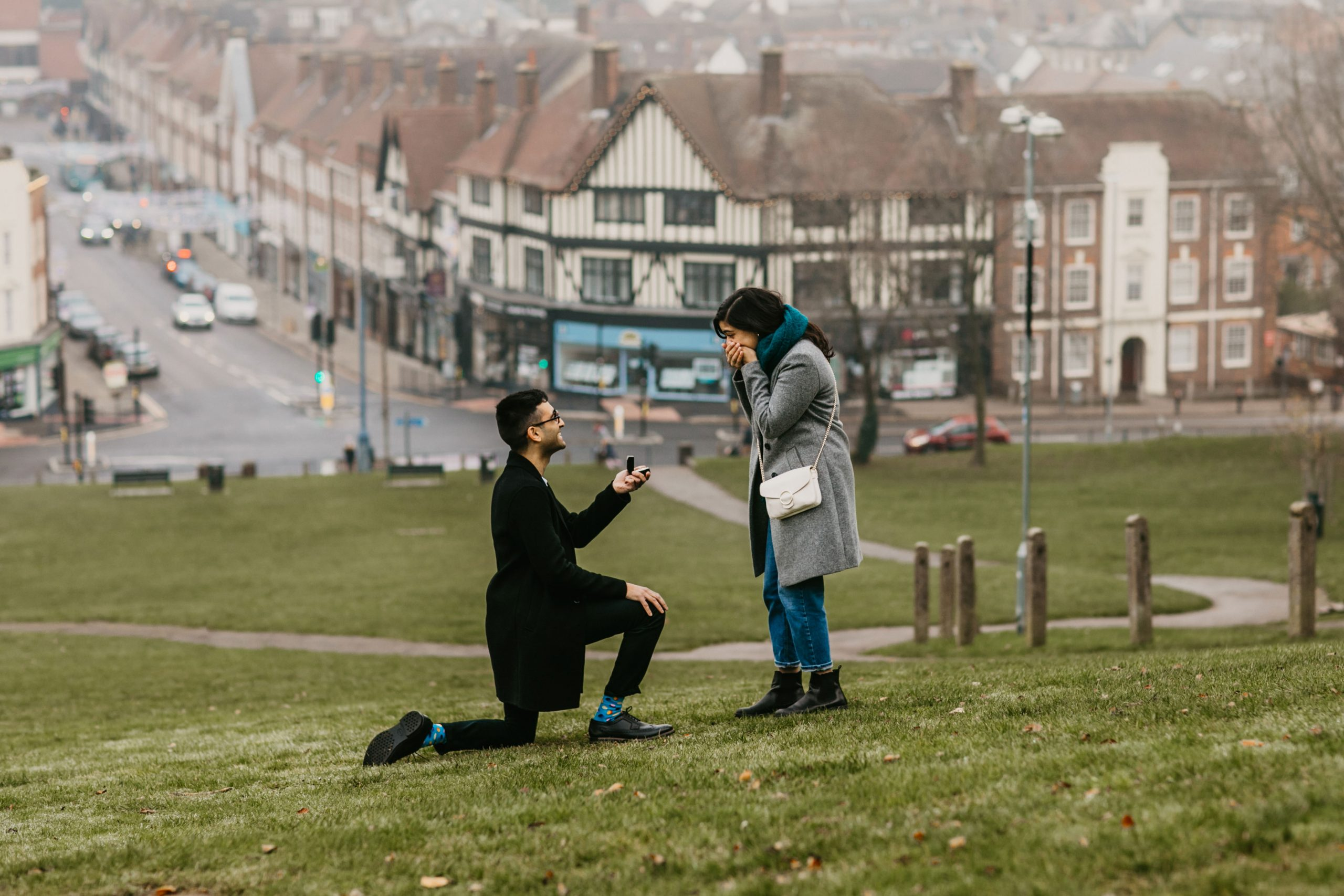 guy on one knee with an engagement ring, proposing to his girlfriend