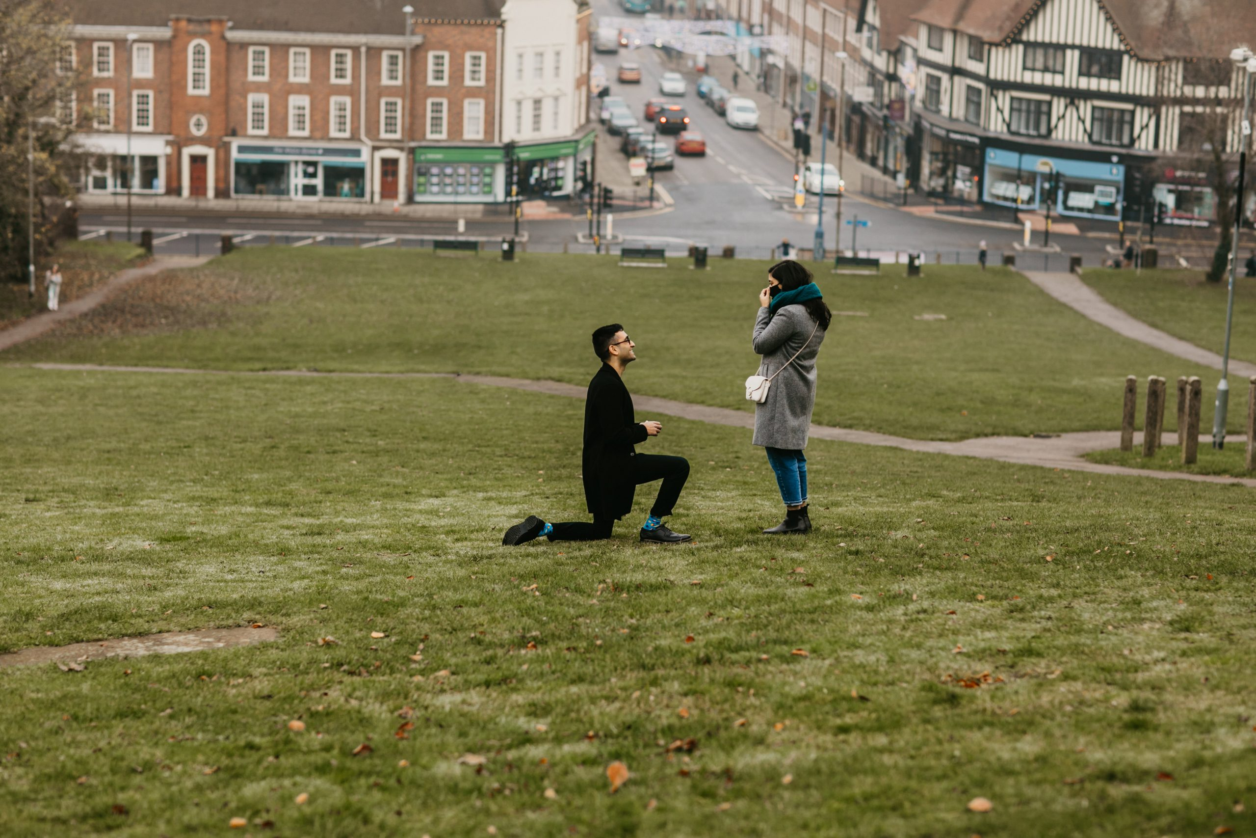 guy in one knee proposing to his girlfriend on a hill near London