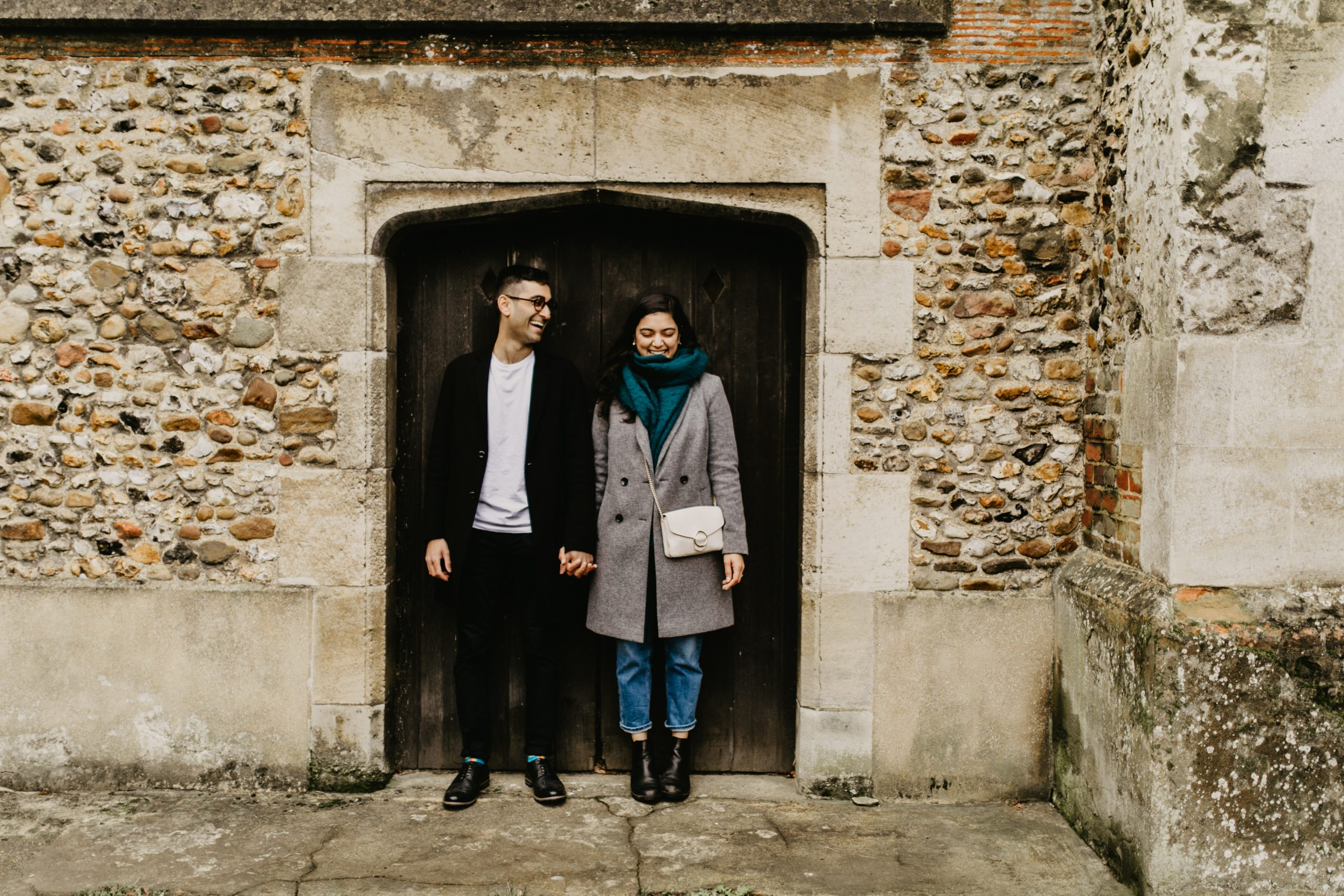 couple by a door during their engagement shoot in 2020